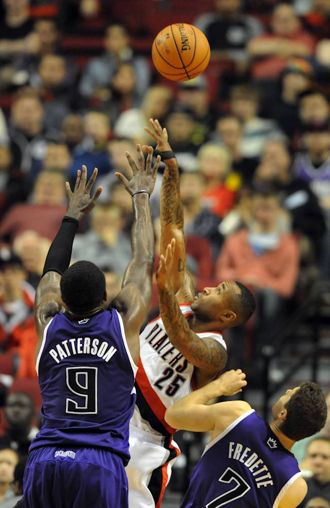 Portland Trail Blazers guard Mo Williams (25) shoots the ball over Sacramento Kings forward Patrick Patterson (9) and Sacramento Kings guard Jimmer Fredette (7) during the second half of an NBA basketball game Sunday, Oct. 20, 2013, in Portland. Portland won 109-105