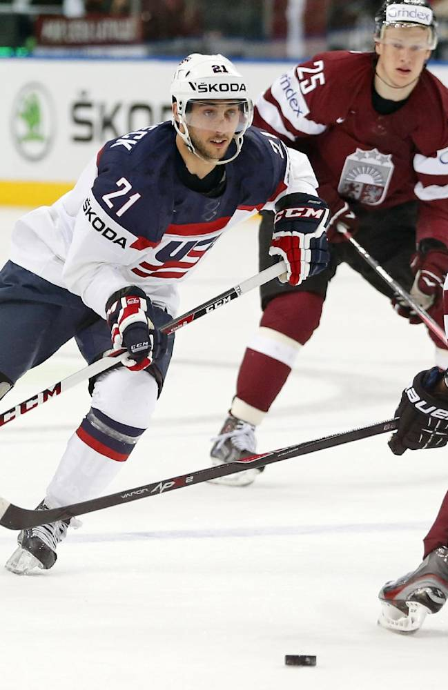 USA forward Vince Trocheck, left, is challenged by Latvia defender Maris Jass during the Group B preliminary round match between USA and Latvia at the Ice Hockey World Championship in Minsk, Belarus, Thursday, May 15, 2014