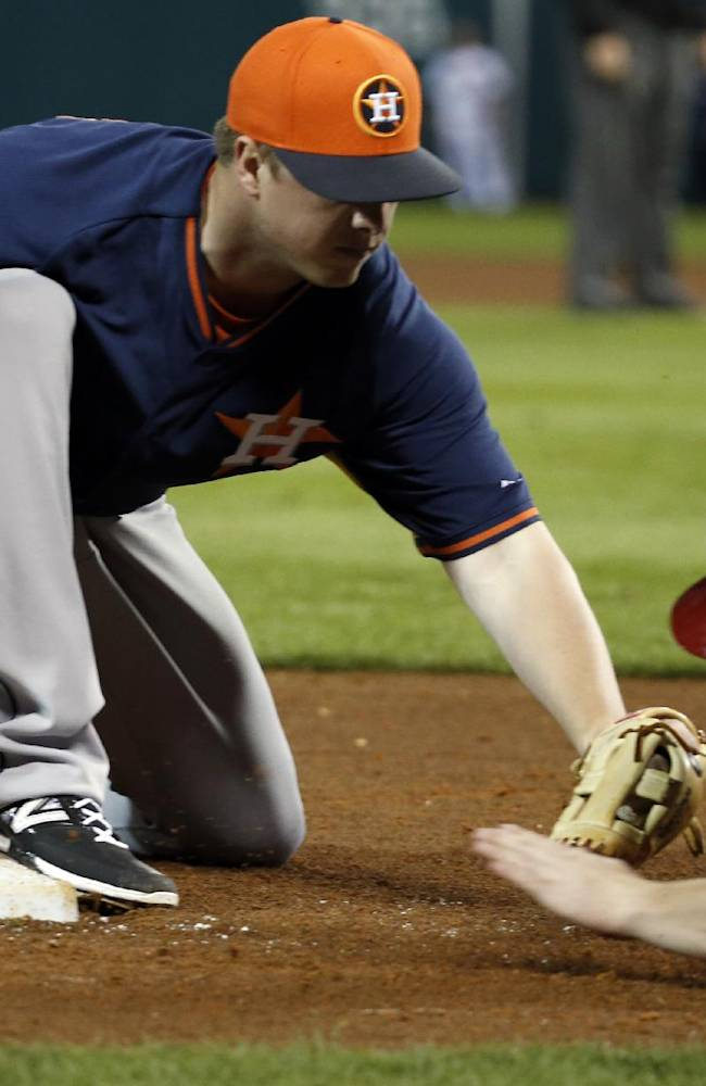 Houston Astros third baseman Matt Dominguez tags out Atlanta Braves' Todd Cunningham as he tries to come back to third base, in the fifth inning of a spring training baseball game, Friday, Feb. 28, 2014, in Kissimmee, Fla. The Astros won 7-5