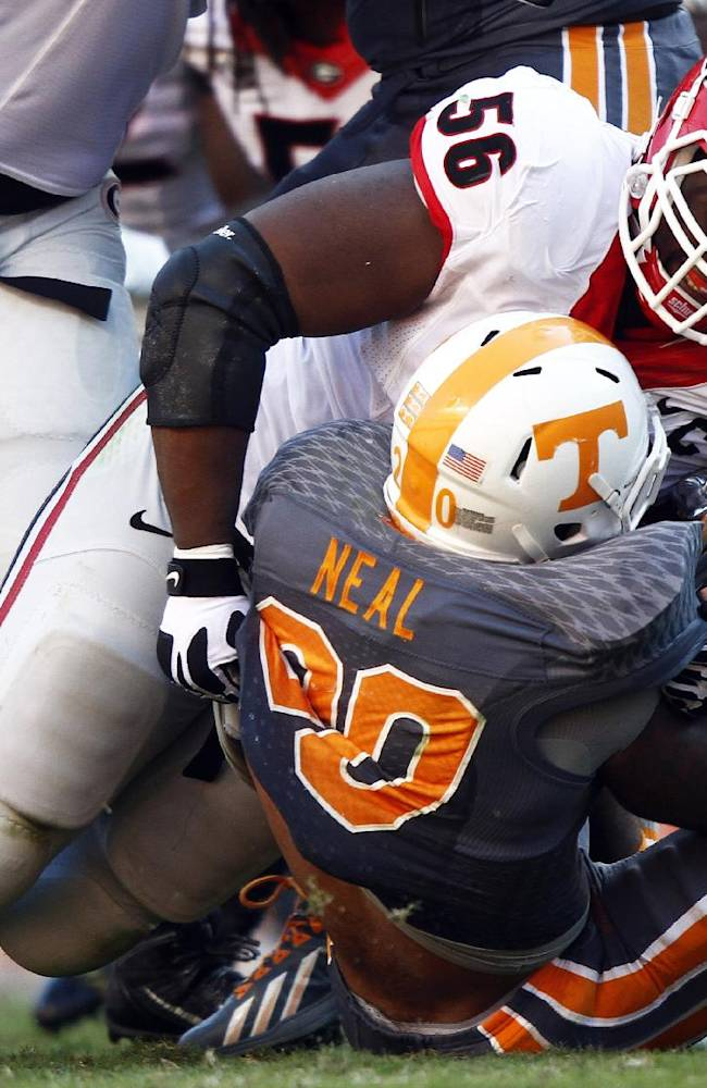 Tennessee's Rajion Neal (20) is tackled by Georgia defensive end Garrison Smith (56) in the second quarter of an NCAA college football game on Saturday, Oct. 5, 2013, in Knoxville, Tenn