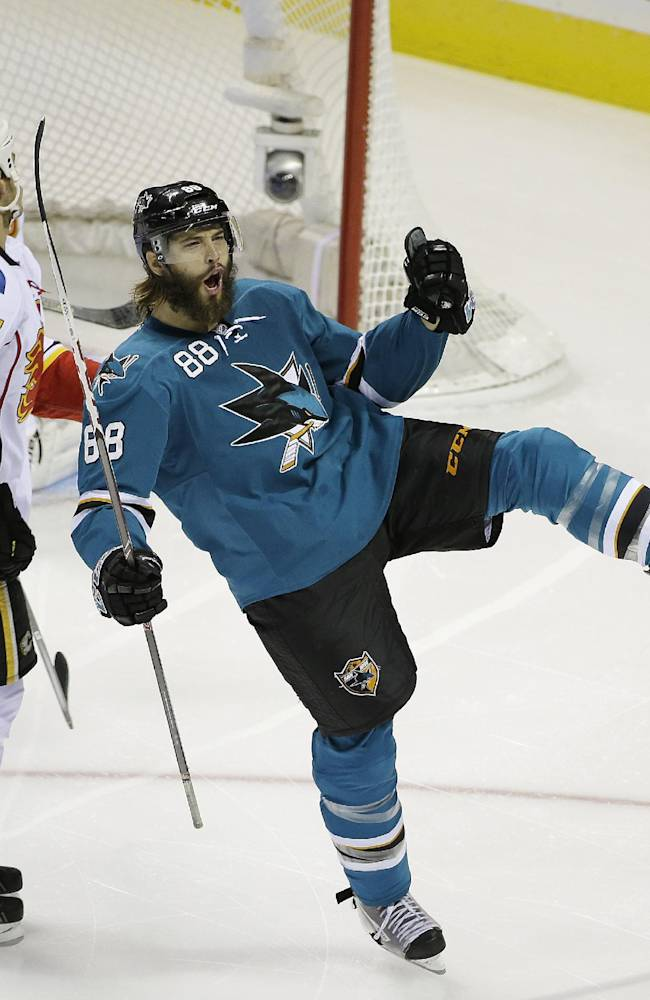 San Jose Sharks right wing Brent Burns reacts after scoring the Sharks' first goal as Calgary Flames goalie Karri Ramo, left, and Calgary Flames center Lance Bouma (17) look on during the first period of an NHL hockey game Saturday, Oct. 19, 2013, in San Jose, Calif