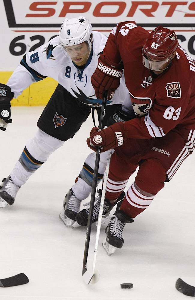Phoenix Coyotes center Mike Ribeiro (63) shields San Jose Sharks center Joe Pavelski (8) from the puck during the third period of an NHL hockey game on Friday, Dec. 27, 2013, in Glendale, Ariz