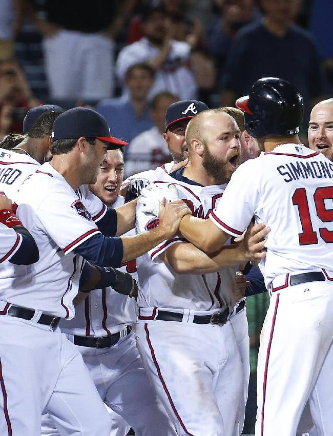 Atlanta Braves catcher Evan Gattis (24), second from right, celebrates with his teammates after hitting a two-run home run in the 10th inning of a baseball game against the Miami Marlins Monday, April 21, 2014 in Atlanta.  Atlanta won 4-2
