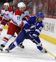 Tampa Bay Lightning's Martin St. Louis (26) tries to move the puck as Carolina Hurricanes' Justin Faulk (27) defends during the first period of an NHL hockey game, Friday, Nov. 1, 2013, in Raleigh, N.C. (AP Photo/Karl B DeBlaker)
