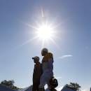 Washington Redskins quarterback Robert Griffin III, right, walks to the field for practice at the team's NFL football training facility, Monday, J