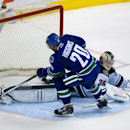 Minnesota Wild's goalie Darcy Kuemper, right, stops Vancouver Canucks' Chris Higgins during a shootout during NHL hockey action in Vancouver, British Columbia on Friday, Feb. 28, 2014 The Associated Press