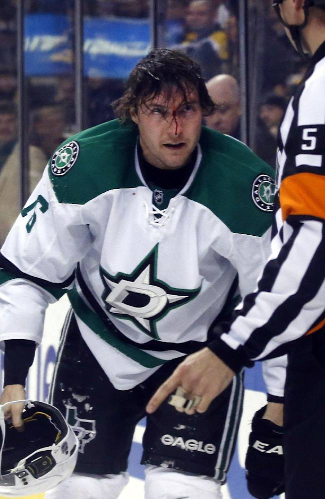 Dallas Stars left wing Ryan Garbutt gathers his equipment to leave the ice with a bloody face during the third period of an NHL hockey game against the Boston Bruins in Boston on Tuesday, Nov. 5, 2013. The Stars won 3-2 in a shootout