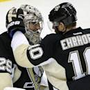 Pittsburgh Penguins goalie Marc-Andre Fleury (29) celebrates with defenseman Christian Ehrhoff (10) after shutting out the Los Angeles Kings 3-0 in an NHL hockey game in Pittsburgh, Thursday, Oct. 30, 2014. (AP Photo/Gene J. Puskar)