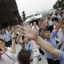 Policemen try to stop photographs from being taken after former England captain David Beckham left Tongji University surrounded by fans in Shanghai June 20, 2013. REUTERS/Aly Song