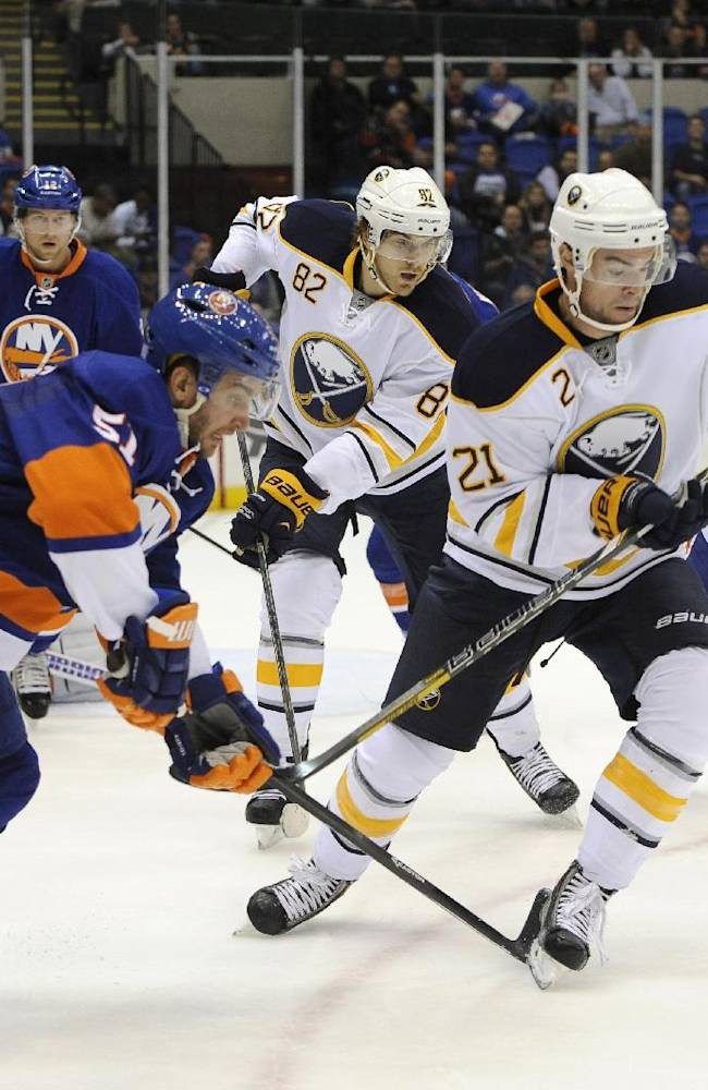 New York Islanders' Frans Nielsen (51), of Denmark, and Buffalo Sabres' Drew Stafford (21) chase the puck as Sabres' Marcus Foligno (82) follows from behind during the first period of an NHL hockey game on Tuesday, Oct. 15, 2013, in Uniondale, N.Y