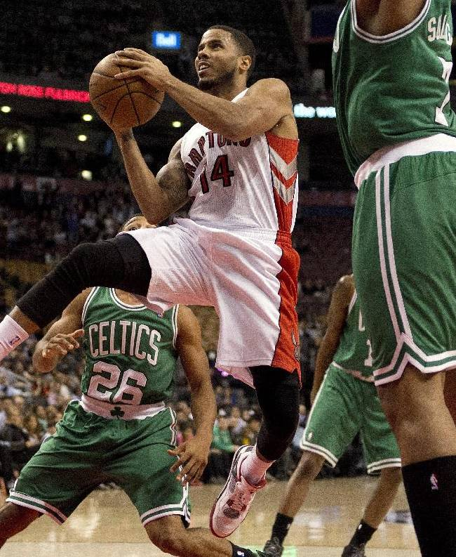 Toronto Raptors guard D.J. Augustin, center, drives to the hoop through the Boston Celtics during the second half of a preseason NBA basketball game in Toronto on Wednesday, Oct. 16, 2013
