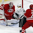 Los Angeles Kings' Dustin Brown (23) has his shot blocked by Carolina Hurricanes goalie Cam Ward (30) with Hurricanes' Justin Faulk (27) defending during the third period of an NHL hockey game in Raleigh, N.C., Sunday, Nov. 2, 2014. Hurricanes won 3-2 The