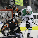 Dallas Stars center Jamie Benn (14) takes a shot on Anaheim Ducks goalie Jonas Hiller (1) as Ducks Ryan Getzlaf (15) applies pressure during the first period of an NHL hockey game in Dallas, Tuesday, Nov. 26, 2013 The Associated Press