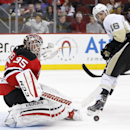 New Jersey Devils goalie Cory Schneider (35) blocks a shot by Pittsburgh Penguins center Brandon Sutter (16) during the first period of an NHL hockey game, Friday, Jan. 30, 2015, in Newark, N.J The Associated Press