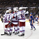 New York Rangers celebrate a goal as Edmonton Oilers' David Perron (57) and goalie Ben Scrivens (30) look on during first period NHL hockey action in Edmonton, Alberta, on Sunday, Dec. 14, 2014 The Associated Press