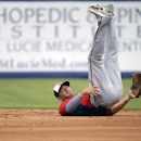 Washington Nationals' Danny Espinosa rolls backwards on a throw to first base after fielding a single by New York Mets' Eric Young Jr. in the first inning of an exhibition spring training baseball game, Thursday, March 27, 2014, in Port St. Lucie, Fla The