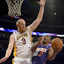 Los Angeles Lakers center Chris Kaman (9) attempts to block Phoenix Suns guard Eric Bledsoe (2) as he goes to the basket in the second half of an NBA basketball game, Sunday, March 30, 2014, in Los Angeles. The Lakers won 115-99 The Associated Press