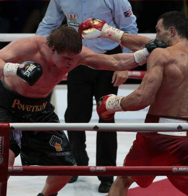 Heavyweight champion Wladimir Klitschko, of Ukraine, right, is hit by Alexander Povetkin, of Russia, in the 11th round of their bout at the Olympic Stadium, in Moscow, Russia, on Saturday, Oct. 5, 2013. Wladimir Klitschko successfully defended his WBA and IBF titles