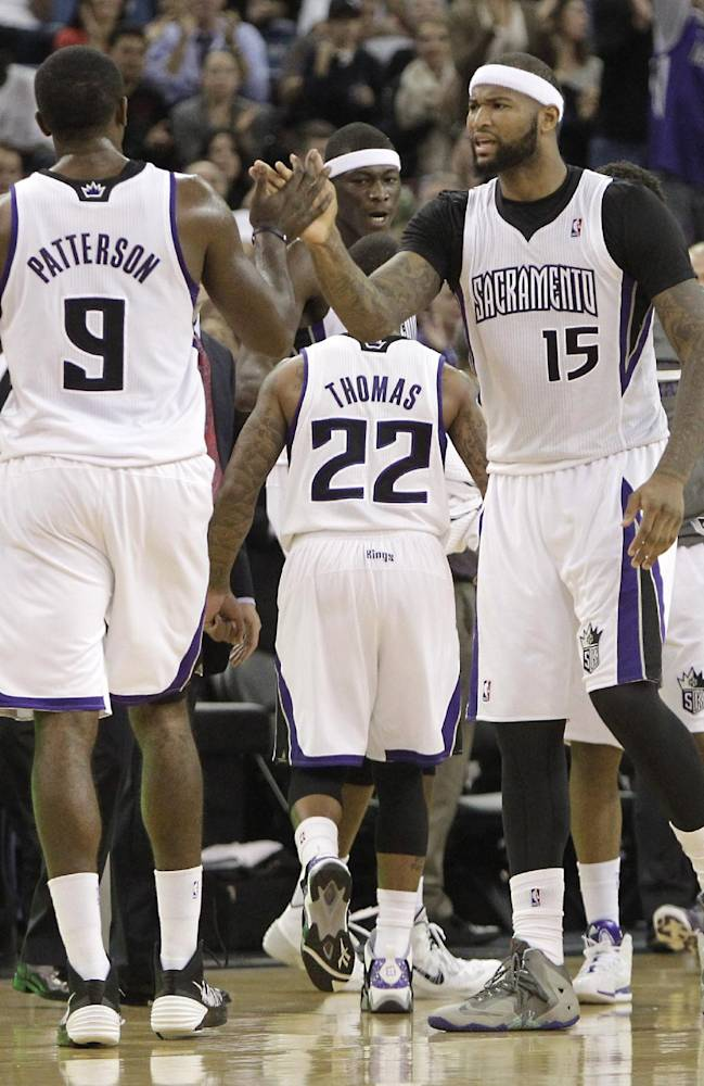 Sacramento Kings center DeMarcus Cousins, right, celebrates with teammate Patrick Patterson during a timeout in the closing moments of an NBA basketball game against the Phoenix Suns in Sacramento, Calif., Tuesday, Nov. 19, 2013.  The Kings won 107-104