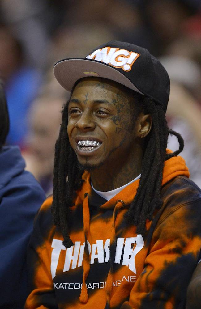 Singer Lil Wayne watches the Los Angeles Clippers play the Houston Rockets during the first half of an NBA basketball game, Wednesday, Feb. 26, 2014, in Los Angeles