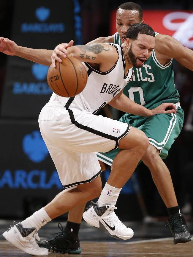Brooklyn Nets guard Deron Williams (8) drives around Boston Celtics guard Avery Bradley (0) in the second half of their their NBA basketball game, Tuesday, Dec. 10, 2013, in New York. Williams scored 25 points for the Nets as they defeated the Celtics 104-96