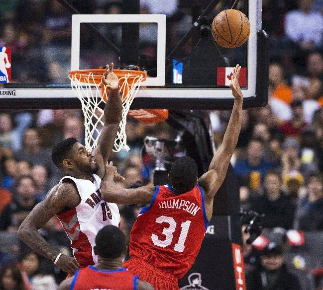 Toronto Raptors' Amir Johnson, left, defends at the net against Philadelphia 76ers' Hollis Thompson during the first half of an NBA basketball game in Toronto on Friday, Dec. 13, 2013