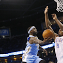Denver Nuggets guard Ty Lawson (3) goes up for a shot in front of Oklahoma City Thunder forward Serge Ibaka (9) in the second quarter of an NBA basketball game in Oklahoma City, Monday, March 24, 2014 The Associated Press