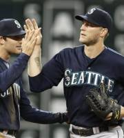 Seattle Mariners' Brad Miller, left, and Michael Saunders celebrate the Mariners' 4-2 win over the Houston Astros in a baseball game Saturday, July 20, 2013, in Houston. (AP Photo/Pat Sullivan)