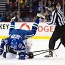 Vancouver Canucks' Daniel Sedin, left, of Sweden, falls on top of Los Angeles Kings' Dustin Brown as linesman Kiel Murchison watches during the first period of an NHL hockey game Saturday, April 5, 2014, in Vancouver, British Columbia The Associated Press