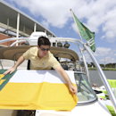 Ryan Leeper adjusts a flag on his friend's power boat tied off on the Brazos River outside new McLane Stadium before an NCAA college football game between SMU and Baylor, Sunday, Aug. 31, 2014, in Waco, Texas. (AP Photo/LM Otero)