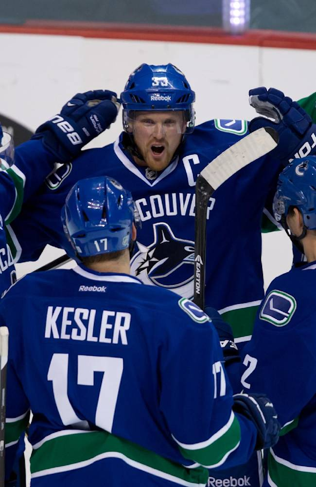 Vancouver Canucks' Henrik Sedin, center, of Sweden, celebrates his goal against the Toronto Maple Leafs with teammates, from left, Daniel Sedin, of Sweden, Ryan Kesler, Dan Hamhuis and Jason Garrison during the first period of an NHL hockey game in Vancouver, British Columbia, on Saturday, Nov. 2, 2013