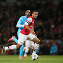 Arsenal s Theo Walcott runs with the ball before shooting at goal during the Group F Champions League soccer match between Arsenal and Marseille at the Emirates stadium in London, Tuesday, Nov. 26, 2013