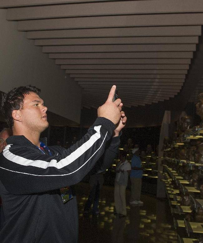 Atlanta Falcons rookie Jake Matthews takes a photo of the bust of Hall of Fame member Mike Munchak , as Arizona Cardinals rookie Troy Niklas watches, during the 2014 NFL Rookie Symposium at the Pro Football Hall of Fame in Canton, Ohio, Wednesday, June 25, 2014