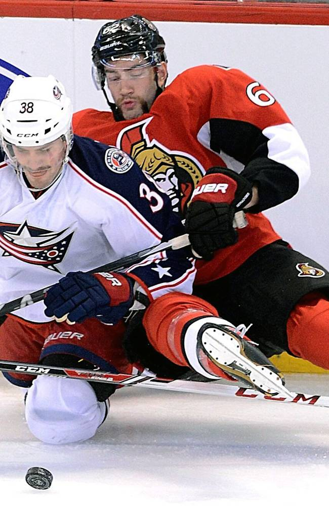Ottawa Senators' Eric Gryba, right, falls to the ice as he attempts to get the puck from Columbus Blue Jackets' Boone Jenner during first-period NHL hockey game action in Ottawa, Ontario, Sunday, Nov. 17, 2013