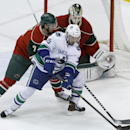 Vancouver Canucks center Brad Richardson, right, controls the puck in front of Minnesota Wild defenseman Jonathon Blum (7) as Minnesota Wild goalie Darcy Kuemper covers the net during the first period of an NHL hockey game in St. Paul, Minn., Wednesday,