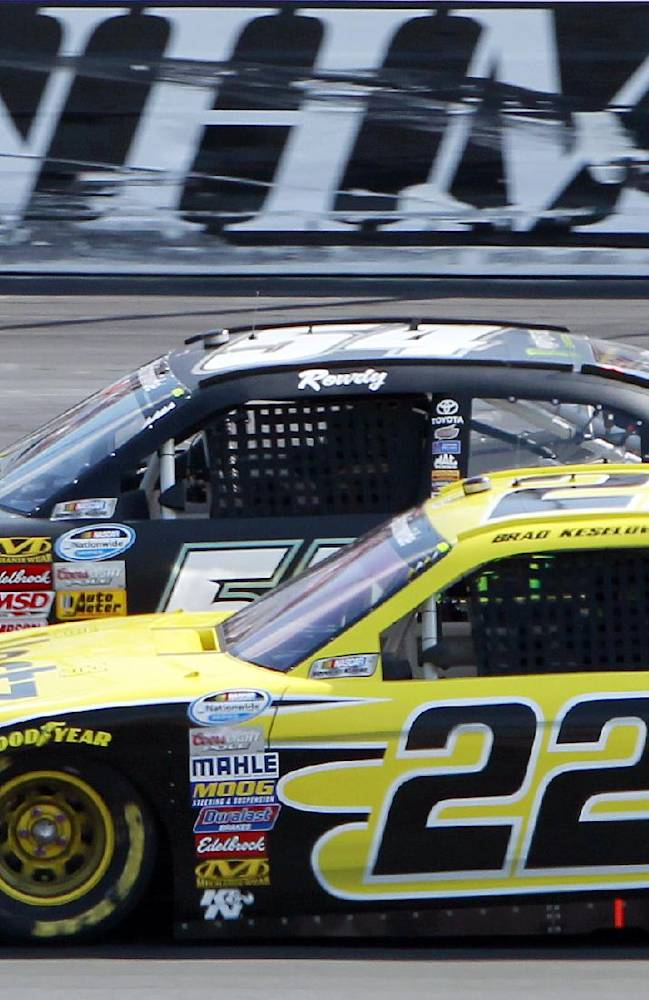 Brad Keselowski (22) slides down to pass Kyle Busch in turn two during the NASCAR Nationwide Series auto race at New Hampshire Motor Speedway Saturday, July 12, 2014, in Loudon, N.H. Keselowski went on to win the race, Busch came in second