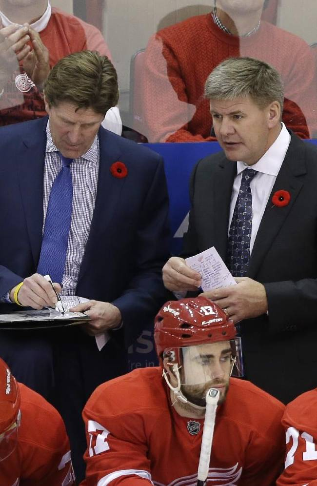 Detroit Red Wings coach Mike Babcock, left, and assistant coach Bill Peters talk during the overtime period of an NHL hockey game against the Tampa Bay Lighting in Detroit, Saturday, Nov. 9, 2013
