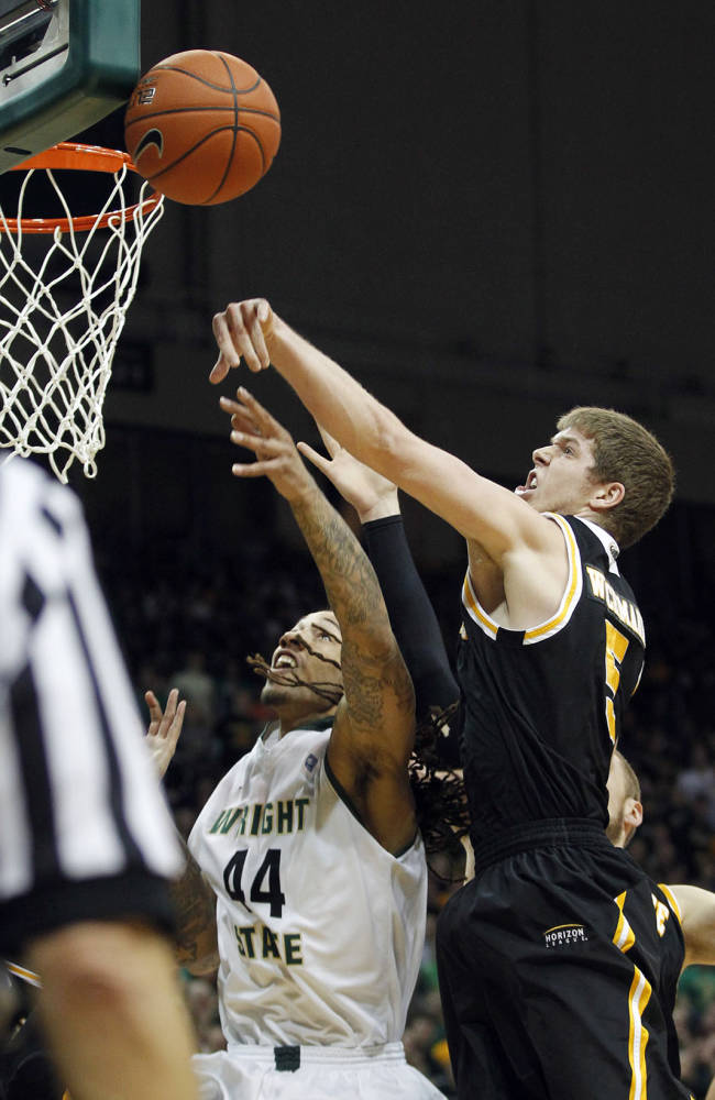 Milwaukee's Cody Whichmann, right, blocks a shot by Wright State's Tavares Sledge during the Horizon League men's tournament championship, Tuesday, March 11, 2014, in Dayton, Ohio