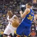Toronto Raptors' Kyle Lowry, left, drives on Golden State Warriors' Stephen Curry during the first half of an NBA basketball game Sunday, March 2, 2014, in Toronto The Associated Press