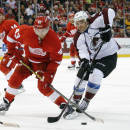 Colorado Avalanche defenseman Zach Redmond (22) ties up Detroit Red Wings center Darren Helm (43) as he tries to shoot during the second period of an NHL hockey game in Detroit Sunday, Dec. 21, 2014. (AP Photo/Paul Sancya)
