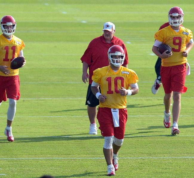 Kansas City Chiefs NFL football quarterbacks Alex Smith (11) Chase Daniel (10) and Tyler Bray (9) hustle to the next drill as head coach Andy Reid follows, Monday morning July 21, 2014, on the Missouri Western State University campus in St. Joseph. Mo