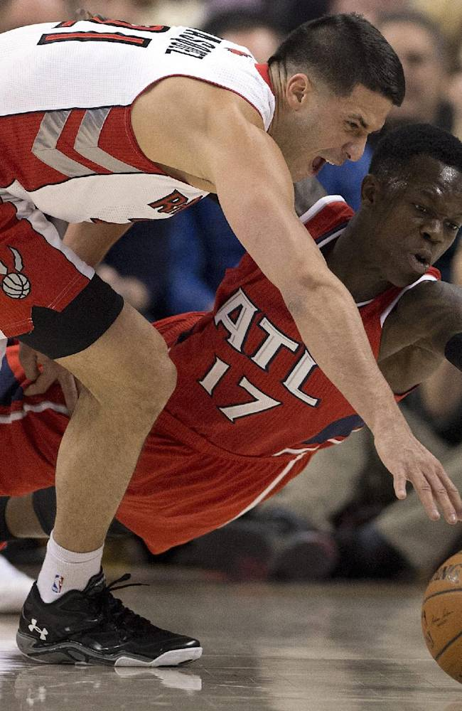 Toronto Raptors guard Greivis Vasquez, left, and Atlanta Hawks guard Dennis Schroder (17) battle for a loose ball during first-half NBA basketball game action in Toronto, Wednesday, Feb. 12, 2014