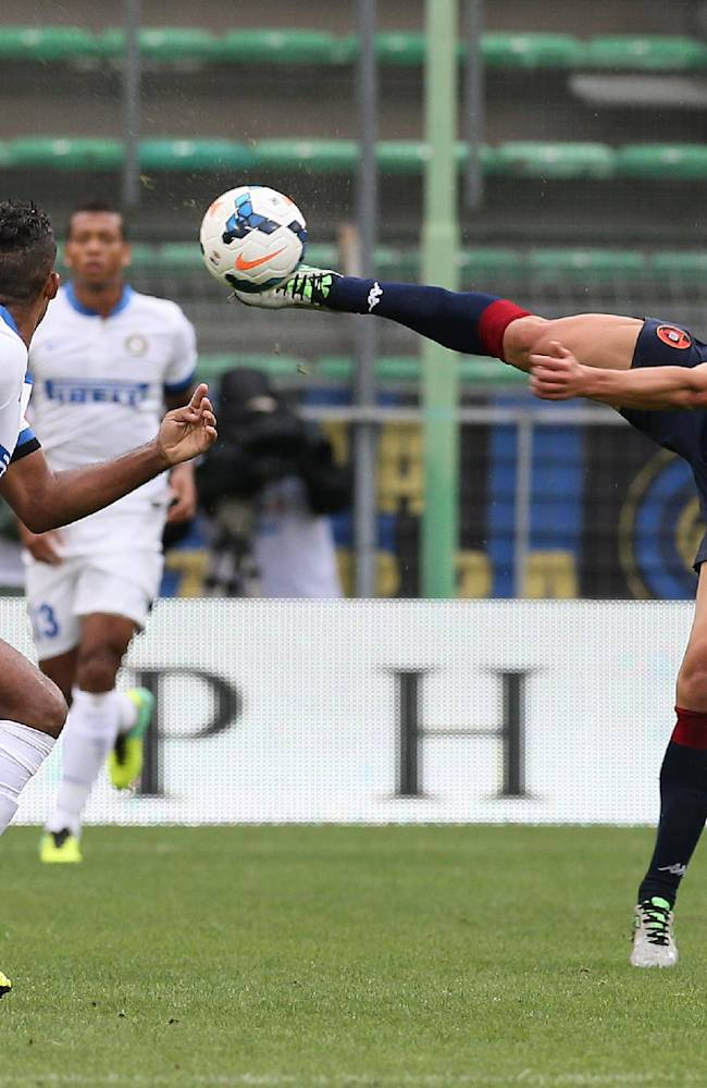 Cagliari's Daniele Dessena, right, reaches for the ball as Inter Milan's Juan watches, during the Serie A soccer match between Cagliari and Inter, at the Nereo Rocco Stadium in Trieste, Italy, Sunday, Sept. 29, 2013