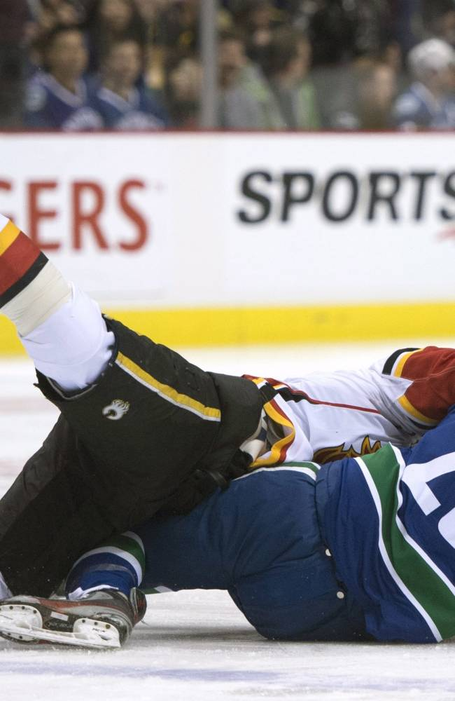 Calgary Flames right wing Brian McGrattan (16) and Vancouver Canucks left wing Tom Sestito (29) fall to the ice as they fight during the first period of an NHL hockey game Saturday, Jan. 18, 2014, in Vancouver, British Columbia