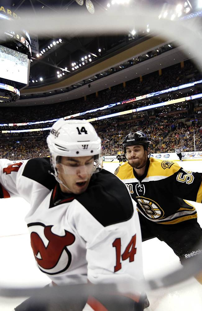 Boston Bruins defenseman Adam McQuaid, right, moves in to check New Jersey Devils' Adam Henrique (14) during the first period of an NHL hockey game in Boston, Saturday, Oct. 26, 2013