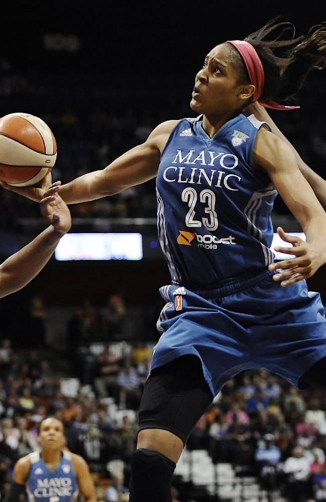 In this July 27, 2014, file photo, Minnesota Lynx's Maya Moore, center, glides to the basket as Connecticut Sun's Kelsey Bone, left, and Chiney Ogwumike, right, defend during the second half of a WNBA basketball game in Uncasville, Conn. Moore has won the WNBA most valuable player award, a person close to the situation told The Associated Press on Wednesday night, Aug. 20, 2014. Moore will receive the award Thursday night in Minnesota before the Lynx face San Antonio in the first game of the Western Conference semifinals