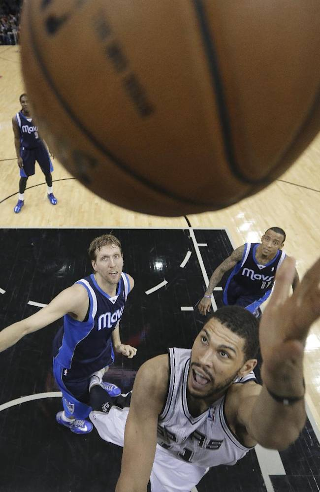 San Antonio Spurs' Jeff Ayres (11) scores as Dallas Mavericks' Dirk Nowitzki, of Germany, and Monta Ellis (11) watch during the second half on an NBA basketball game, Wednesday, Jan. 8, 2014, in San Antonio. San Antonio won 112-90