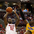 Ohio State's Sam Thompson (12) goes up for a shot against Morehead State's Marcus Fuggins (11) and Corban Collins (3) during the first half of an NCAA college basketball game in Columbus, Ohio, Saturday, Dec. 13, 2014. (AP Photo/Paul Vernon)