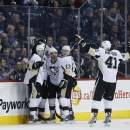Pittsburgh Penguins' Christian Ehrhoff (10), Teddy Purcell (16), Steve Downie (23), Steve Downie (23) and Robert Bortuzzo (41) celebrate Purcell's goal against the Winnipeg Jets during the second period of an NHL hockey game Thursday, Nov. 6, 2014, in Win