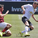 Manchester United's Tom Cleverley, right, evades coverage by AS Roma's Alessandro Florenzi during an exhibition soccer match at Mile High Stadium in Denver, Saturday, July 26, 2014